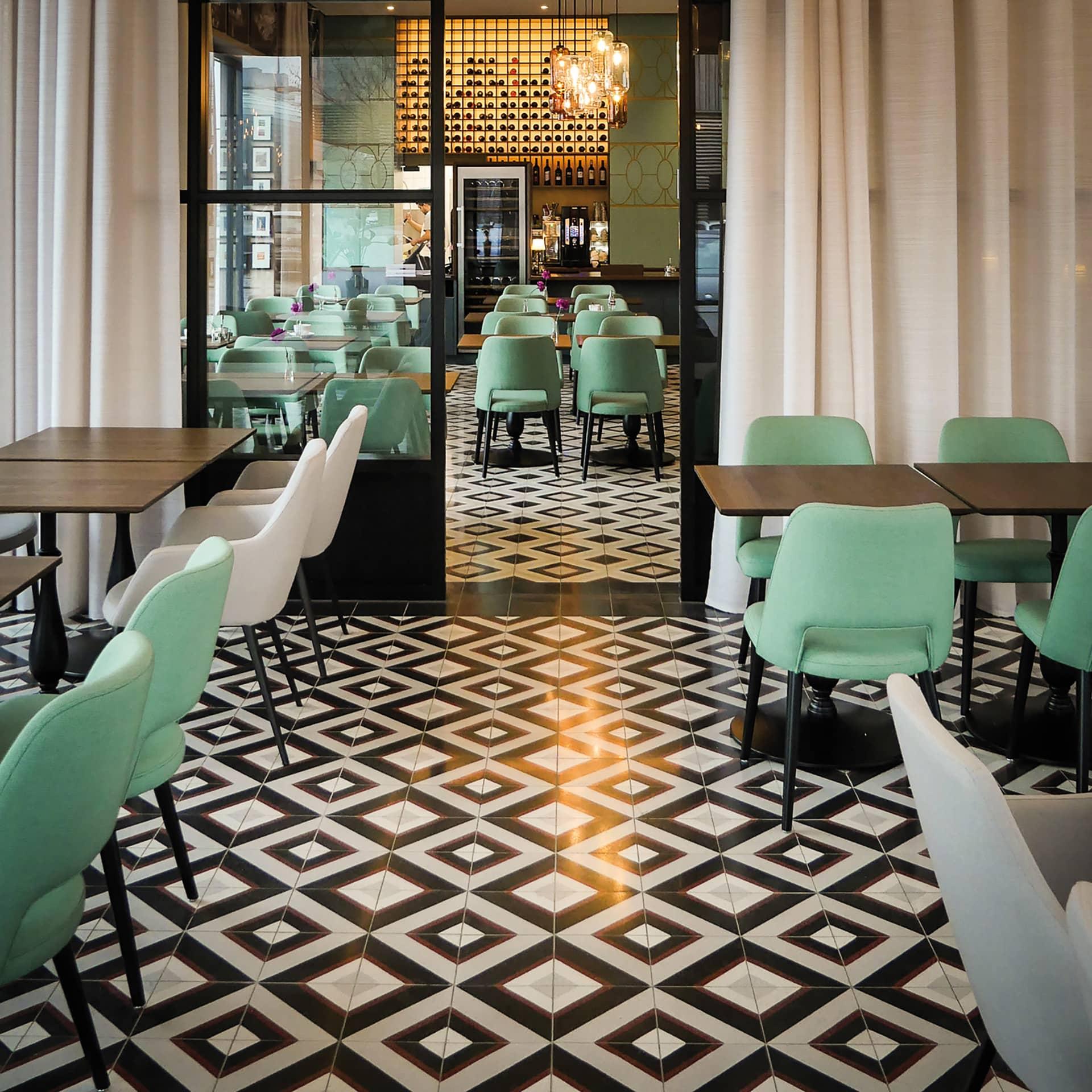 VIA Zementfliese N° 711052 im Restaurant mit grünen Stühlen